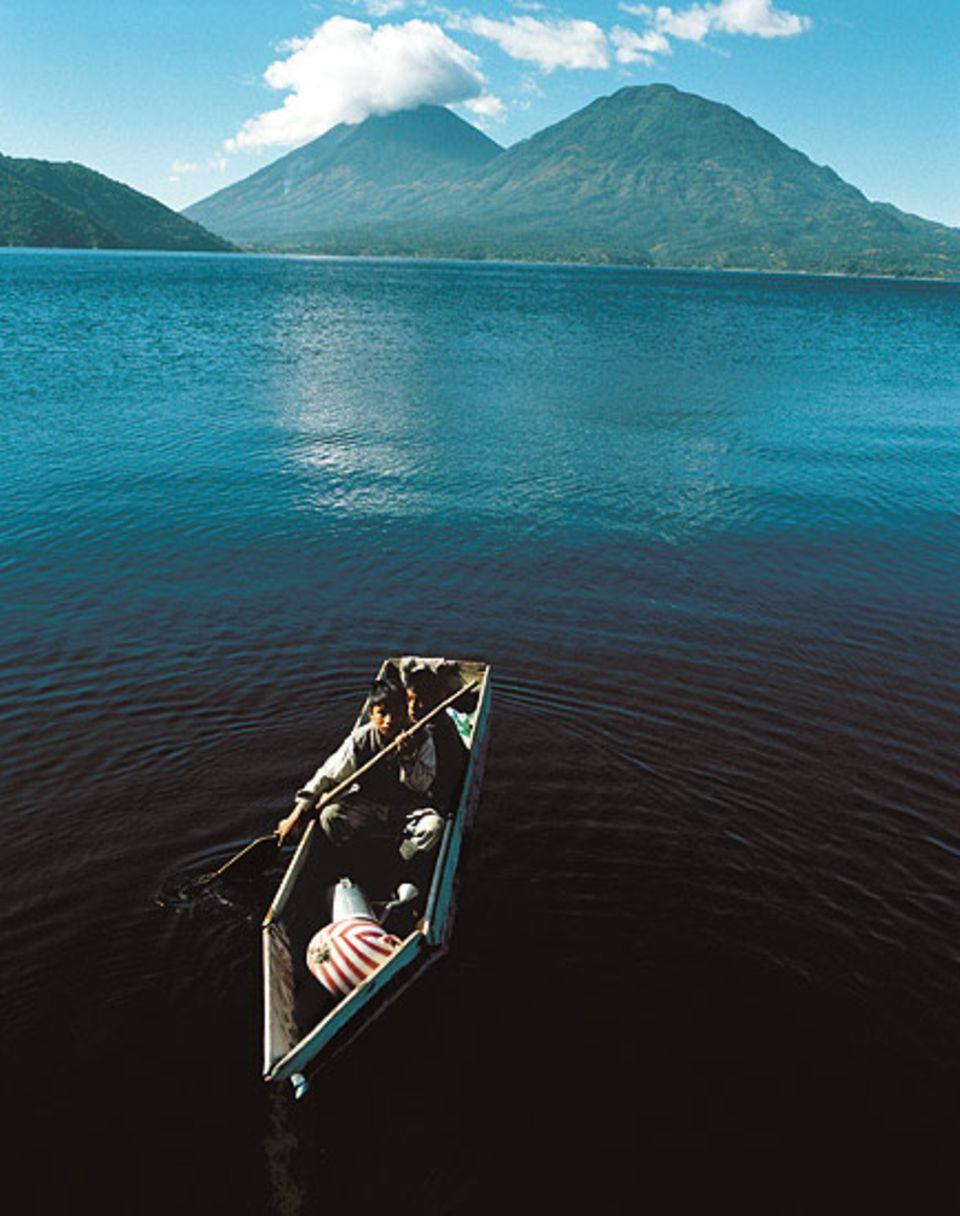 Wie die Urväter: Maya-Jungen steuern ein Kanu über den Atitlán-See - der bevorzugte Verkehrsweg in der Region