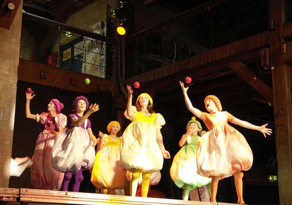 Kunterbuntes Farbenspiel: Eine Gruppe kleiner, bunter Kugelwesen jongliert mit Bällen