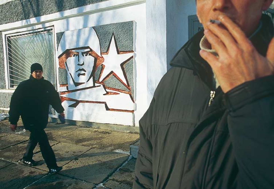 """Sozialistischer Supermann: Im Schlammgrau der Straßen von Tiraspol wirken die Mauerbilder aus sowjetischer Zeit wie monumentale Comiczeichnungen. """"Wir Transnistrier mögen das"""", behaupten die lokalen Politiker"""