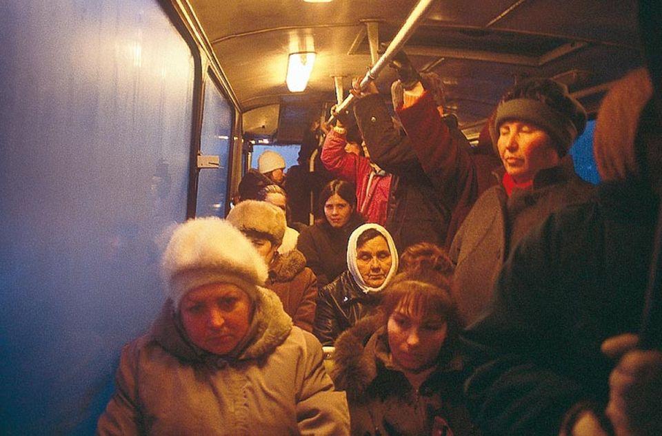 """Morgendliche Trübsal: Omnibusse fahren die Arbeiter in die Fabriken. """"Oft müssen wir monatelang auf die Auszahlung unserer Löhne warten!"""", schimpfen sie"""