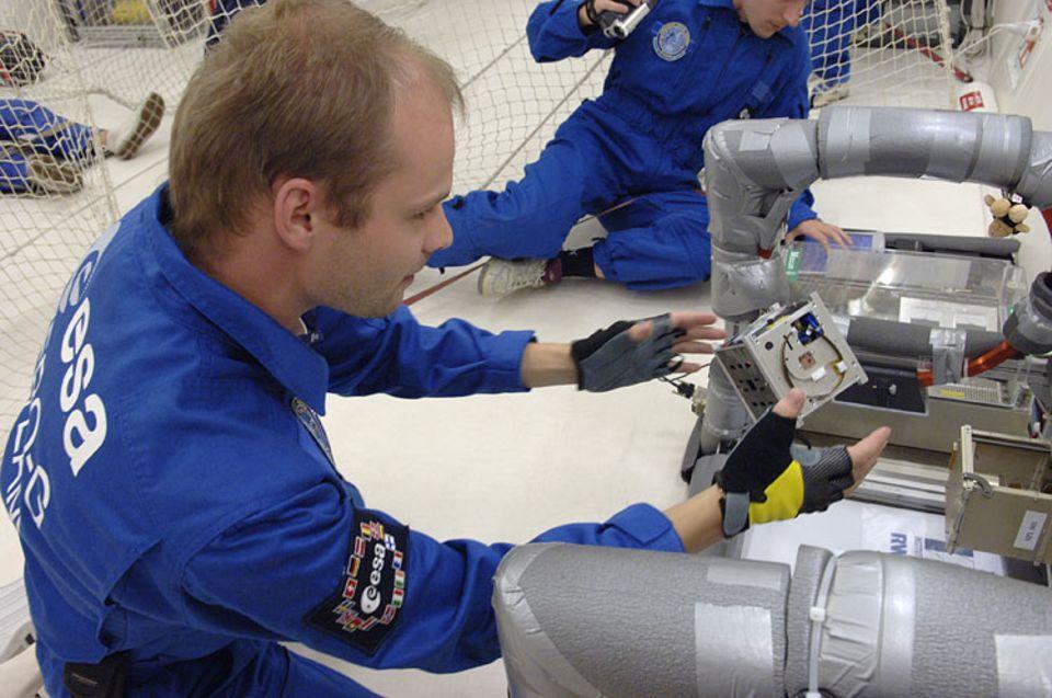 """Parabelflug: Rico Preisker (vorn) und Alexander Korff von der RWTH Aachen setzen einen Miniatur-Satelliten im """"Weltall"""" aus"""
