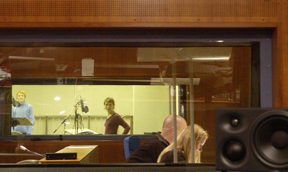 Regieraum und Aufnahmeraum sind durch ein großes Fenster voneinander getrennt. Über Mikrofone können die Sprecher mit dem Team im Regieraum reden