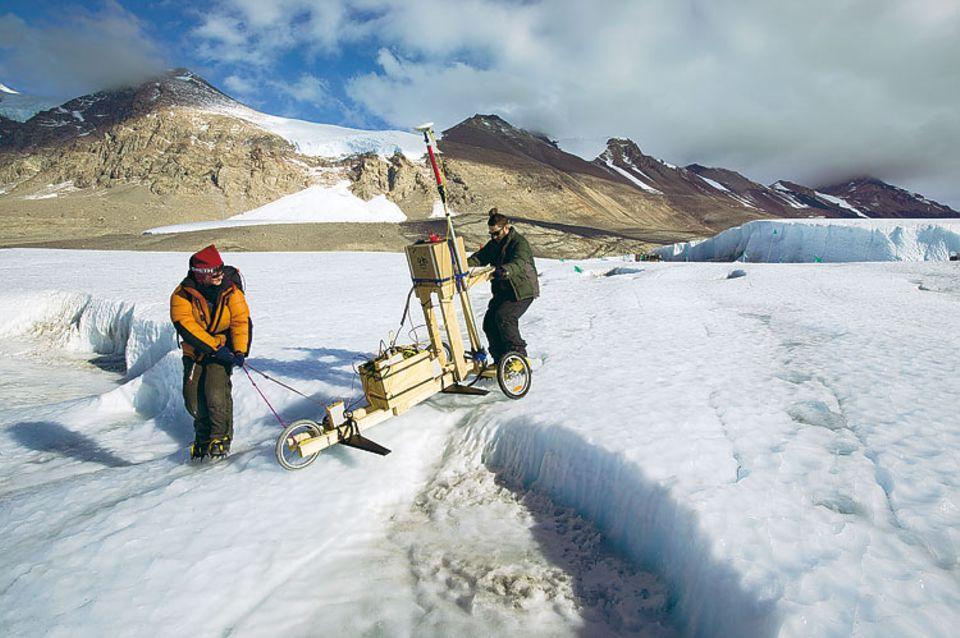 Forscher haben einen Mineral-See entdeckt, zu dessen Kartierung sie ein Radargerät auf einer Holzkarre über das Eis ziehen