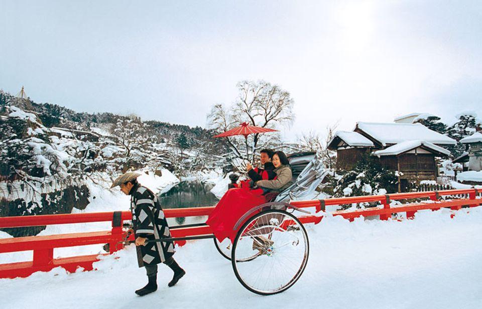 Japanischer Ziehweg: Abgeschirmt von jeglicher Hektik, genießen Touristen eine Rikscha-Fahrt durch die tief verschneite Bergstadt Takayama
