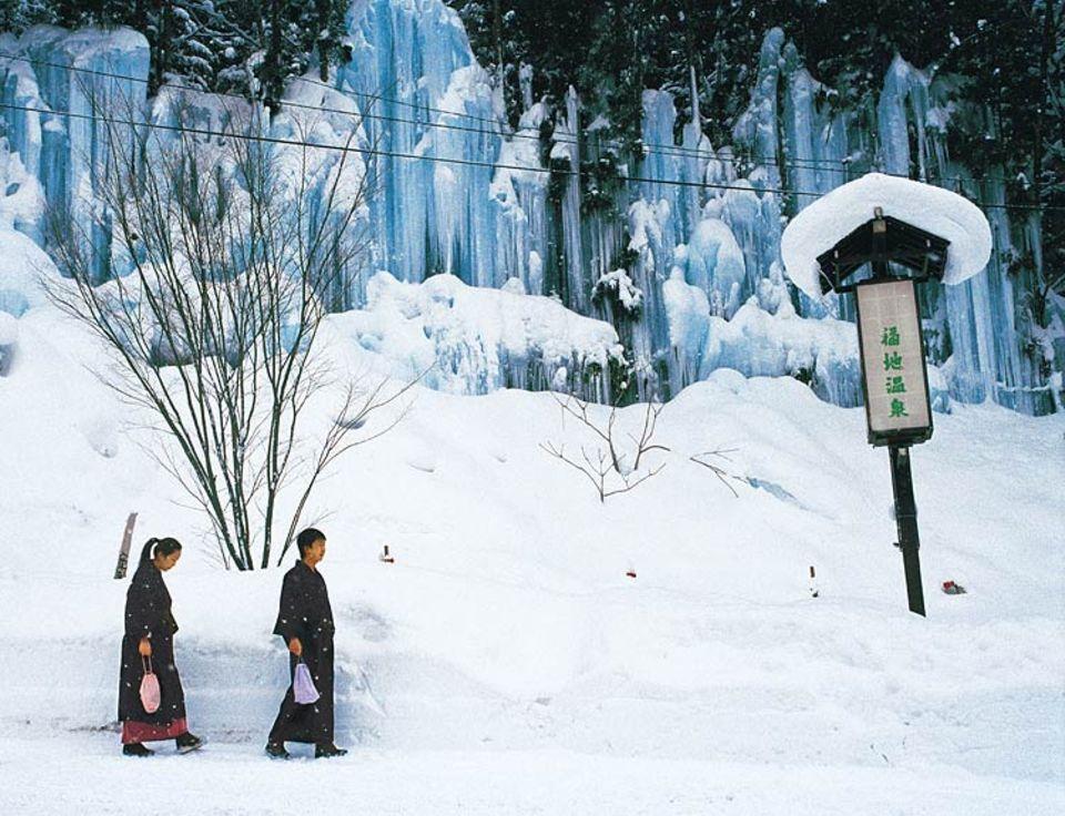 Eislaufen In den Bergen: Bei Hirayu kann es einem heiß und kalt werden - wie diesem Paar auf dem Weg von der Quelle zum Hotel