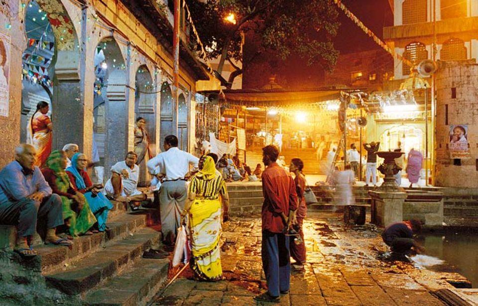 Beim Zwischenhalt in Nashik, nordöstlich von Mumbai, erleben die Reisenden den Alltag Indiens: Gläubige, die sich am Fluss Godavari rituell reinigen, Passanten im trägen abendlichen Plausch und das für den Subkontinent so typische weiche Licht