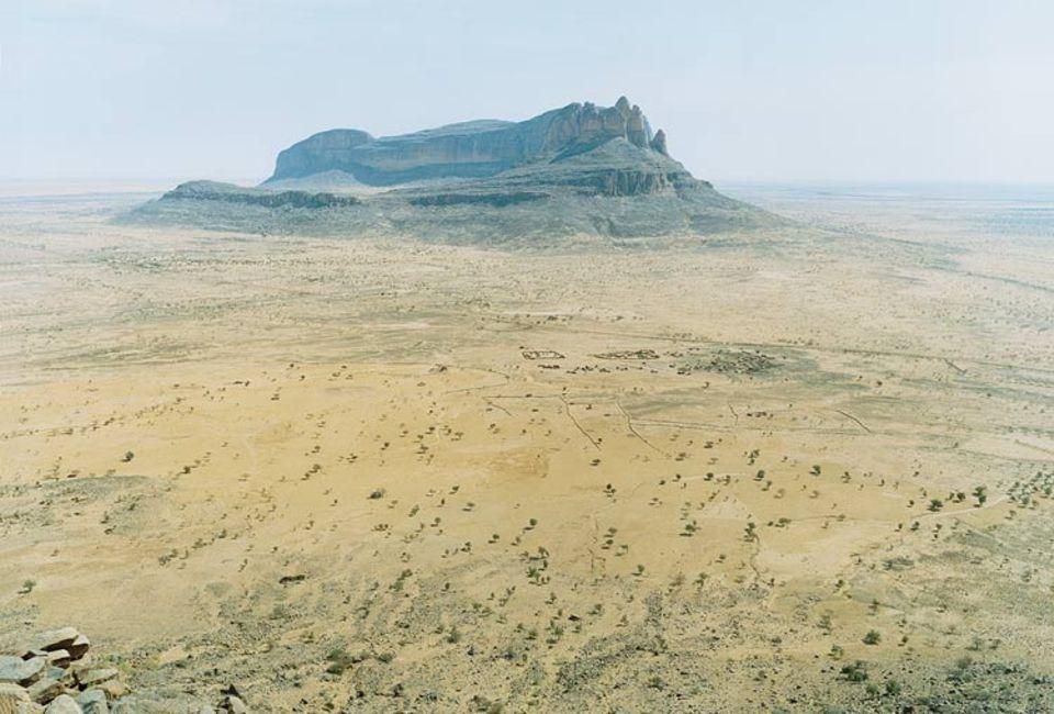 """Mali: De Farbe scheint aus der Landschaft zu weichen, Sahel (""""Wüstenufer"""") heißt der schier endlose Saum der Sahara. Wind und Sand fegen durch das Hombori-Gebirge, eine dürre, spärlich besiedelte Region mit gewaltigen Tafelbergen im Süden Malis"""