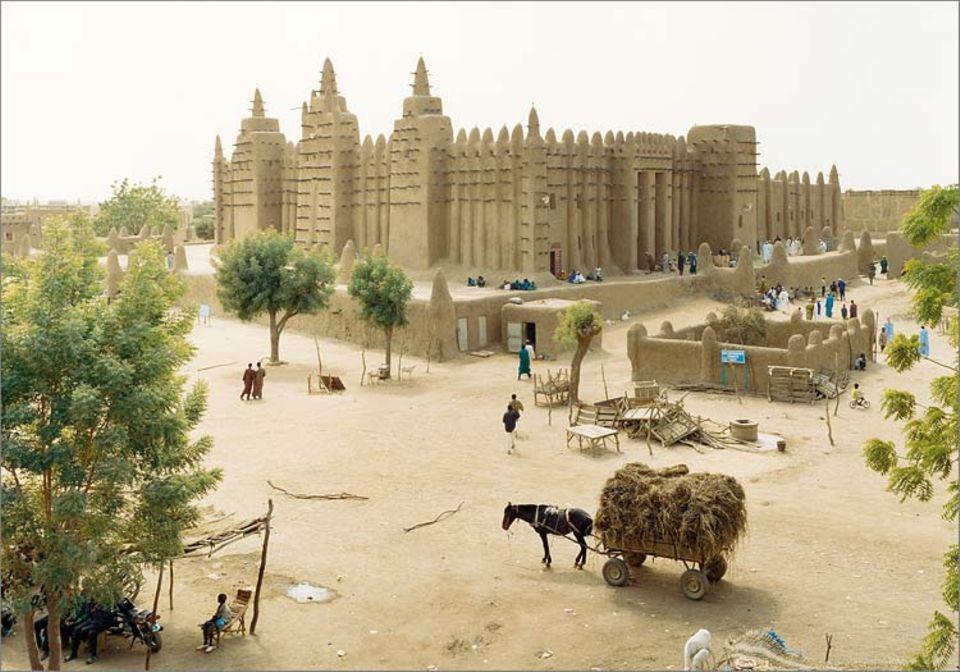 Mali: Zum Freitagsgebet versammeln sich die Gläubigen in der Moschee von Djenné - ein Bild wie aus lange vergangenen Zeiten. Der mächteig Bau erhält alljährlich einen neuen Lehmüberzug; als Leitern nutzen die Arbeiter die Holzbalken, die aus der Fassade ragen