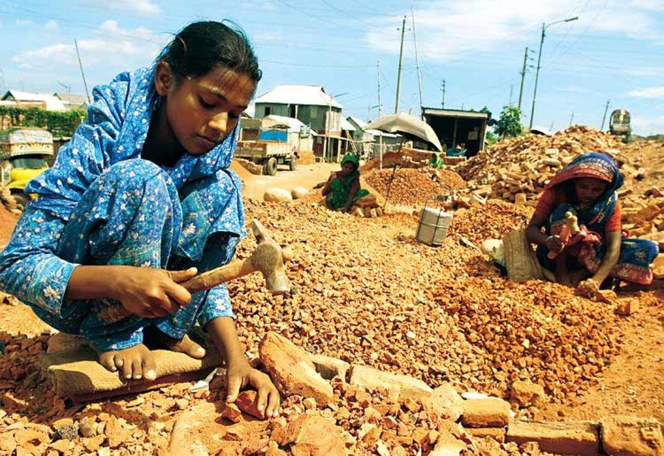 An manchen Tagen zertrümmert Rokeya (vorn) neun Stunden lang Ziegelsteine aus Abbruchhäusern in kleine Stücke. Seit über zwei Jahren muss die Elfjährige so Geld verdienen