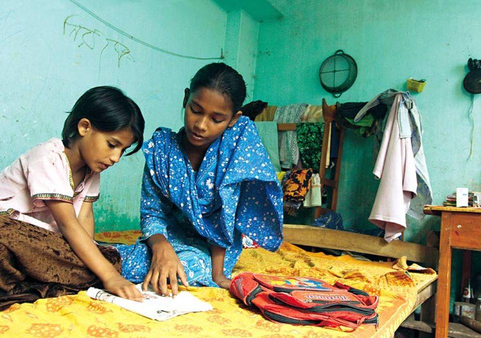 Hilfsbereit: Rokeya übt zu Hause mit ihrer achtjährigen Schwester Aisha lesen. Die Jüngere möchte später auch auf die UNICEF-Schule gehen