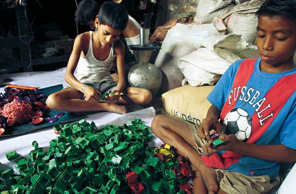 Kinderarbeit für Kinderspielzeug: Shaikat (vorn) steckt seit fast zwei Jahren in einer dunklen Werkstatt Plastikautos zusammen. Sein ganzer Stolz ist das T-Shirt mit deutscher Schrift und Fußballbild