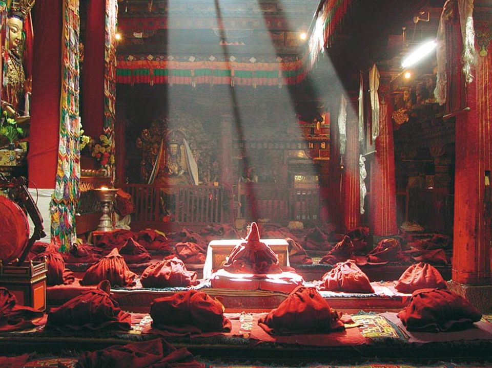 """Der Jokhang-Tempel, heiligster Ort Tibets: Die Kutten der Mönche liegen bereit, gleich beginnt das Gebet. Das Bild von Andreas Hofem aus Heidelberg ist der Sieger des Online-Fotowettbewerbs auf GEO.de. """"Intensive rote Farben, dazu die Sonnenstrahlen im Zentrum - dem Fotografen ist es gelungen, den Tempel besonders poetisch in Szene zu setzen"""", lautet die Begründung des GEO-Bildredakteurs Markus Seewald"""