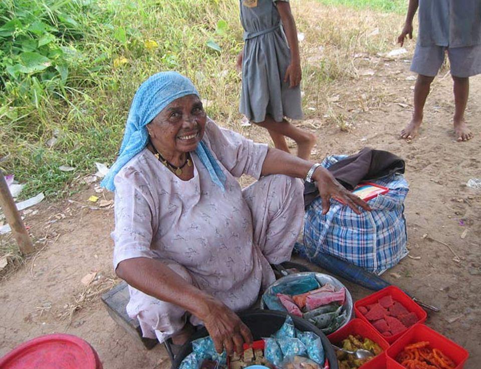 Baini wartet jeden Tag auf die Schulkinder, um ihre Süßigkeiten zu verkaufen