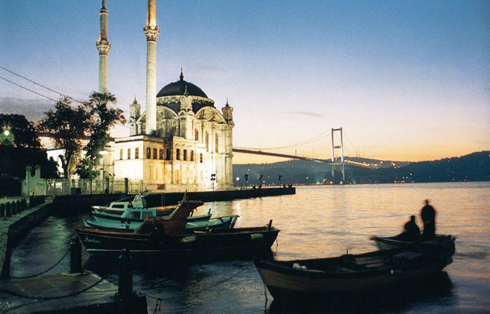 Am Bosporus erhebt sich die Ortaköy-Moschee, die Brücke im Hintergrund verbindet Europa mit Asien. Fischer kehren in ihren Booten zurück - Idylle mitten in Metropolis