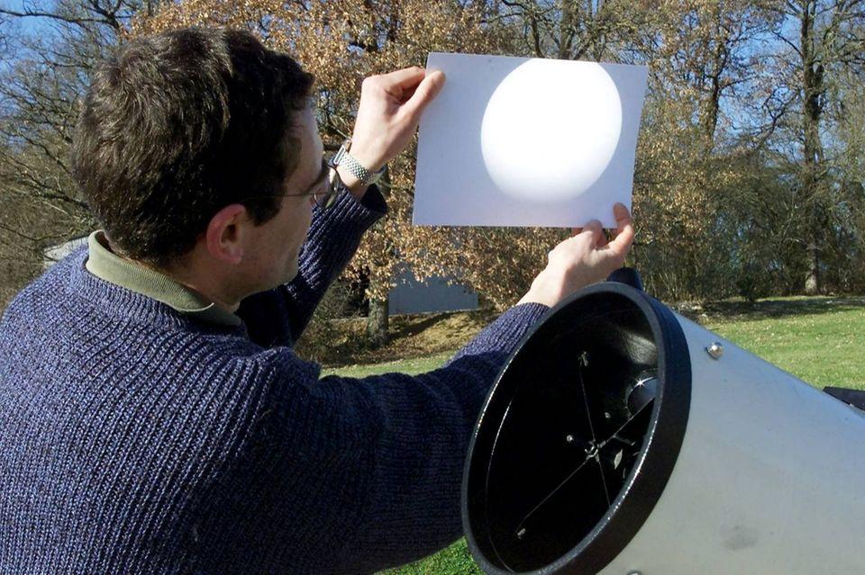 Ein Astronom zeigt ein Bild von einer Sonnenfinsternis auf dem Blatt