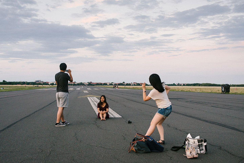 Touristen machen Fotos auf dem Tempelhofer Feld in Berlin