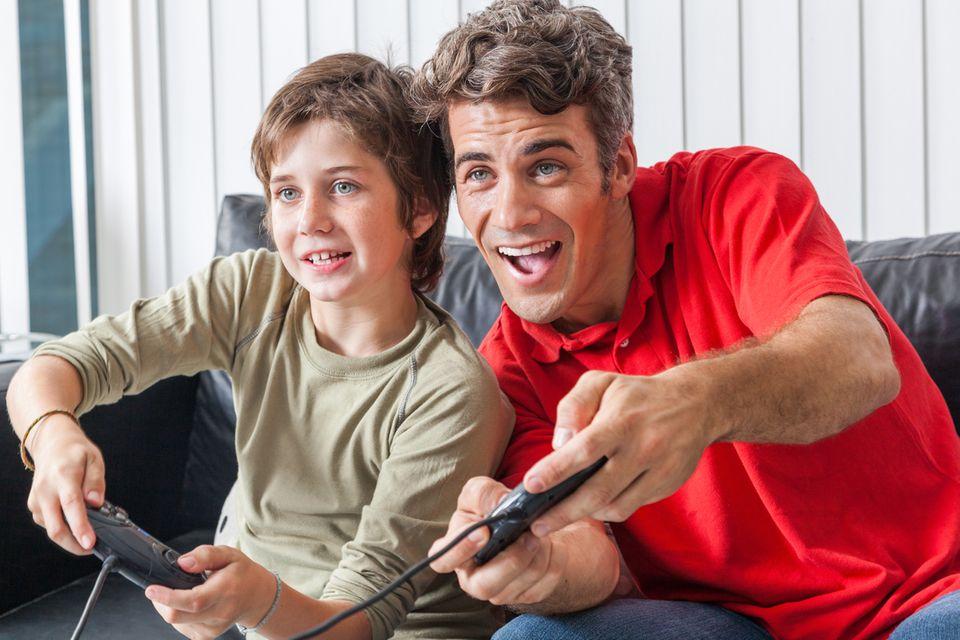 Familie spielt Videospiele auf der Konsole am Fernseher