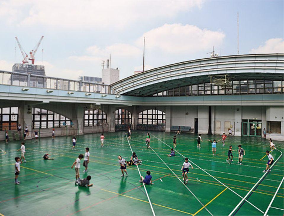 Kindheit: Lernzentrum: Nirgendwo geht es in Schulen lebendiger zu als auf dem Pausenhof: Hier können Kinder mit Freunden herumtollen und ihren Bewegungsdrang ausleben. Das Projekt »Playground« des Engländers James Mollison zeigt Lehranstalten rund um die Welt - hier das Obergeschoss einer Grundschule in Tokio mit aufschiebbarem Dach