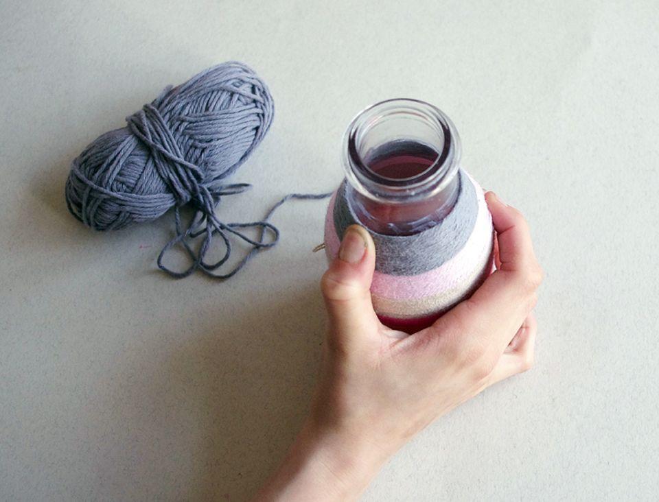 Basteln: Führt den Wollfaden Stück für Stück um das Gefäß herum
