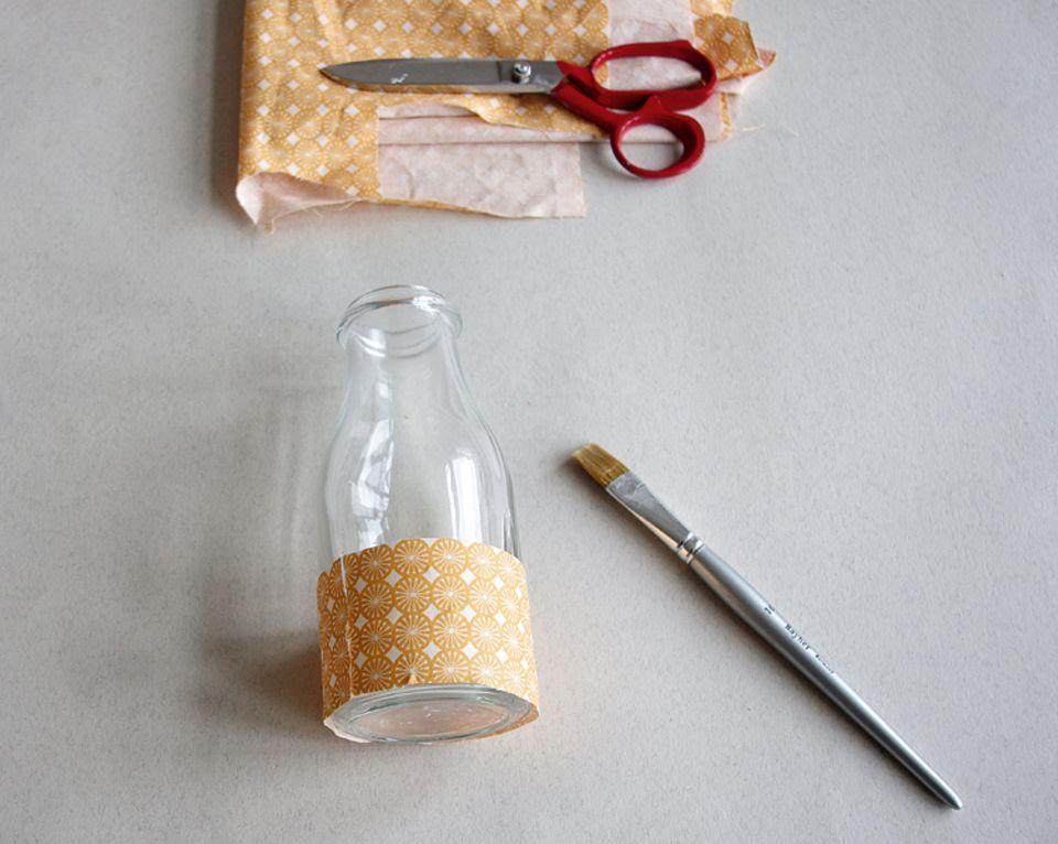 Basteln: Schneide Stoffstreifen auf die richtige Länge zurecht und beklebe damit das Gefäß