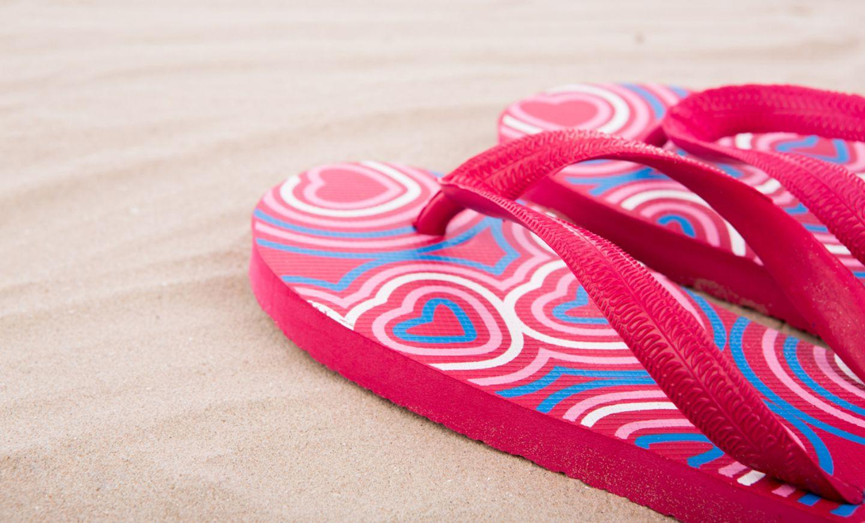Pinke Flipflops im Sand