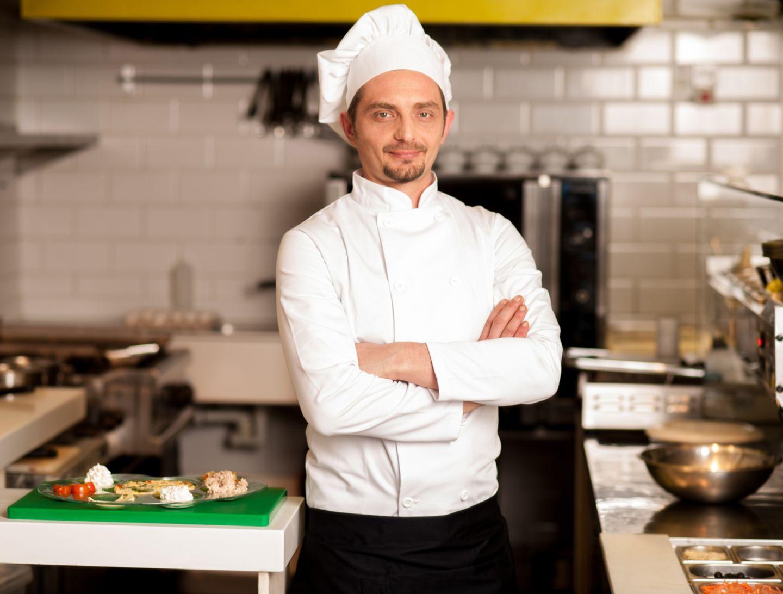 Junger Koch steht in seiner Küche