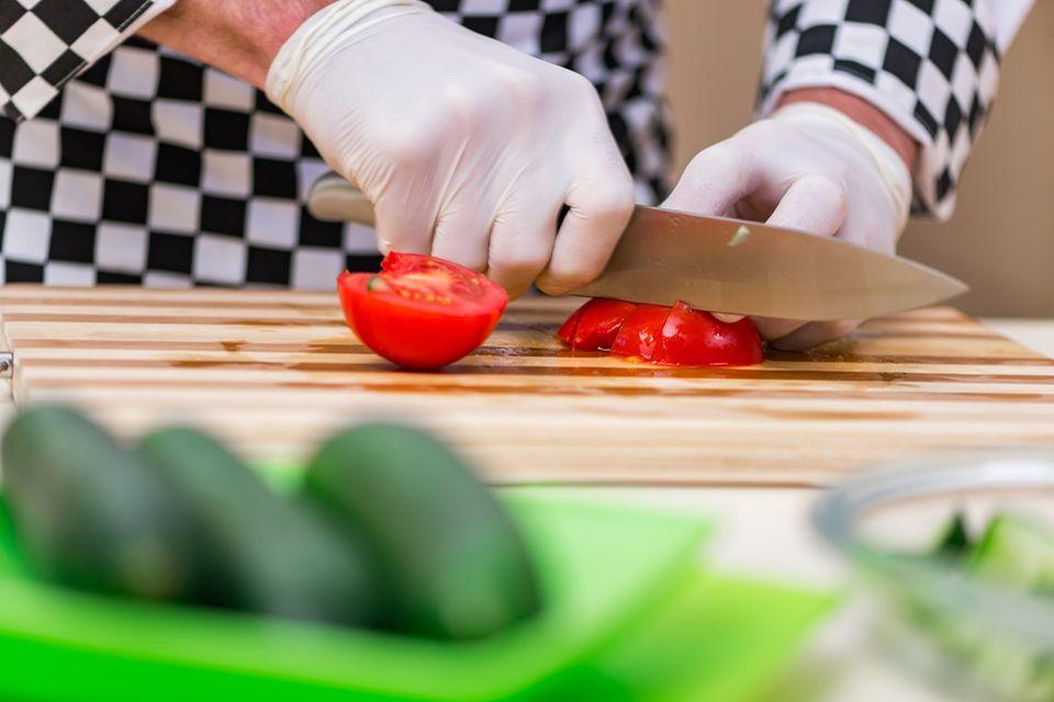 Beruf: Ein Koch schneidet Tomaten