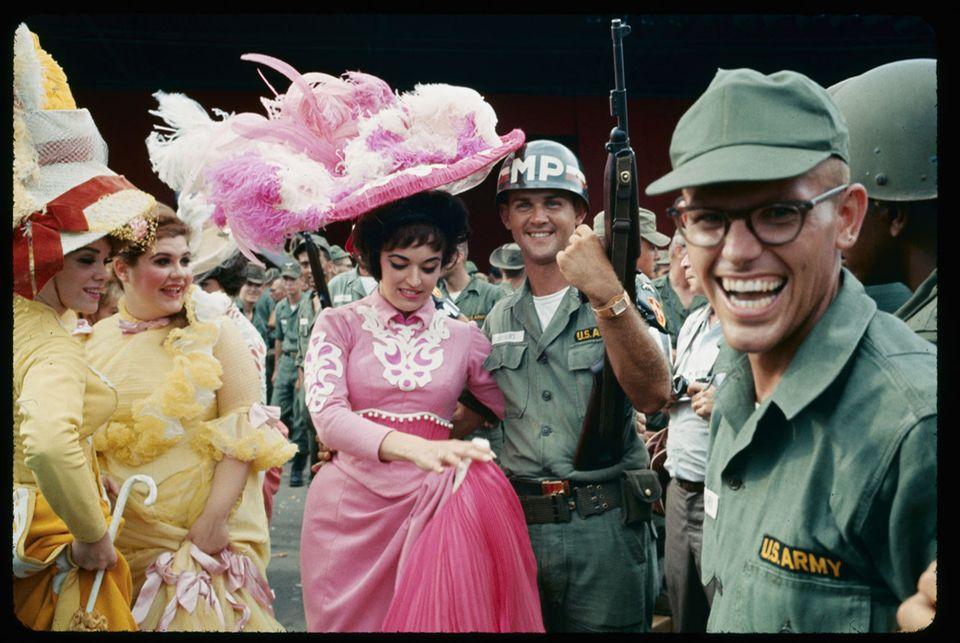 Der Wahnsinn des Krieges : Eine fast unwirkliche Erinnerung an die Heimat: Soldaten lassen sich mit Darstellerinnen des Musicals »Hello, Dolly!« fotografieren