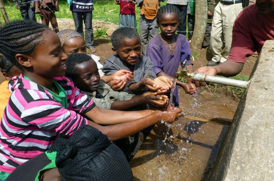 Die Kinder in der Gemeinde Tagera sehen im Oktober 2013 zum ersten Mal sauberes Wasser aus einer Leitung fließen