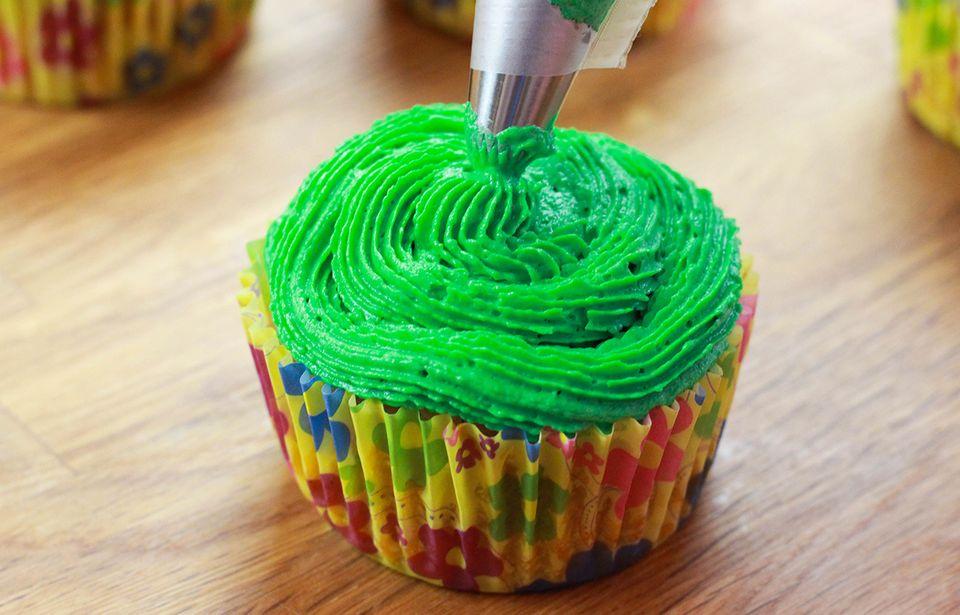 Die grüne Buttercreme auf die Cakepops spritzen