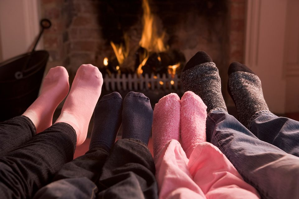 Eine Familie sitzt Zuhause in dicken Socken vor dem Kamin