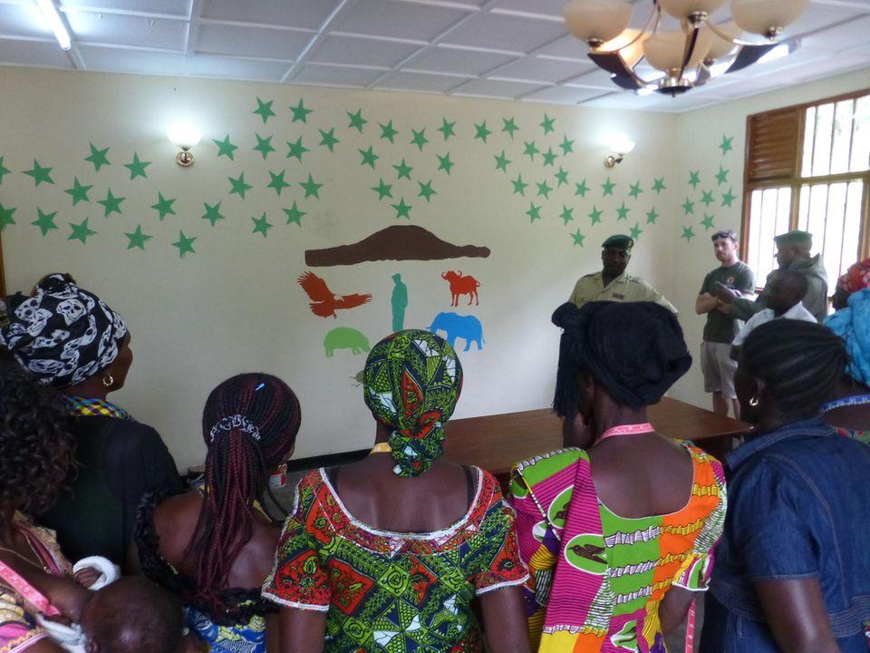 Demokratische Republik Kongo: Bei der Einweihung erklärt Innocent Mburanumwe das Wandgemälde im künftigen Fortbildungsraum: Jeder der 154 grünen Sterne steht für einen im Dienst getöteten Ranger von Virunga