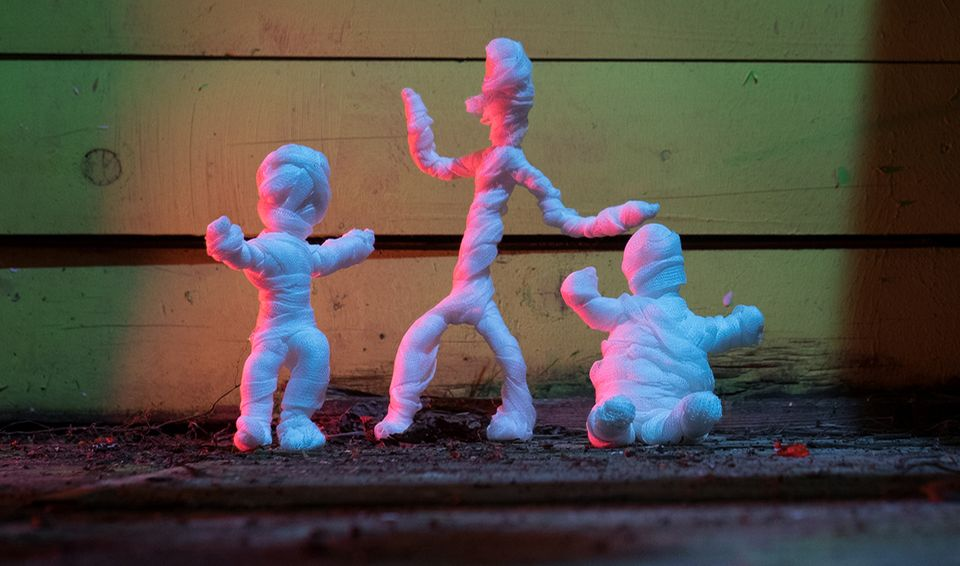 Drei Mumien vor einer Wand