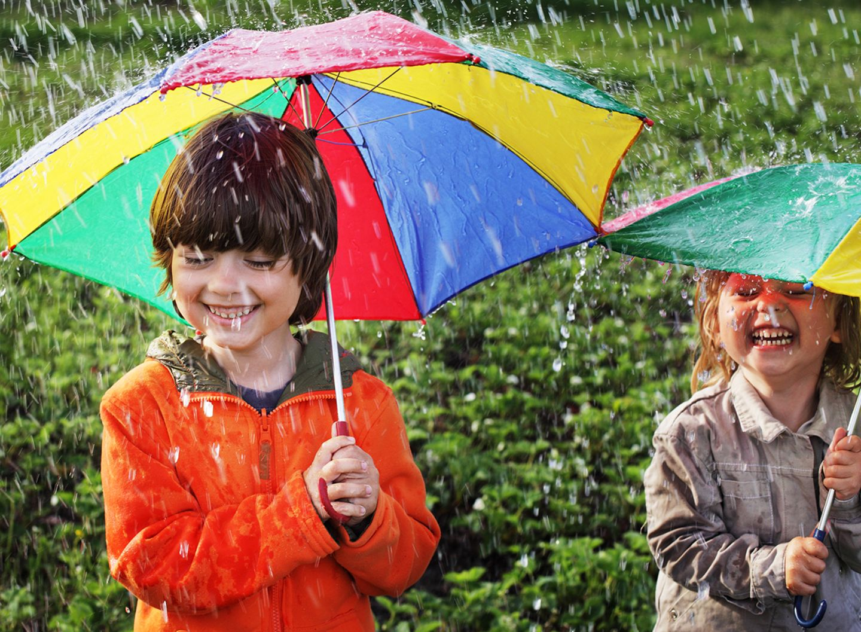 Zwei Kinder unter Regenschirmen