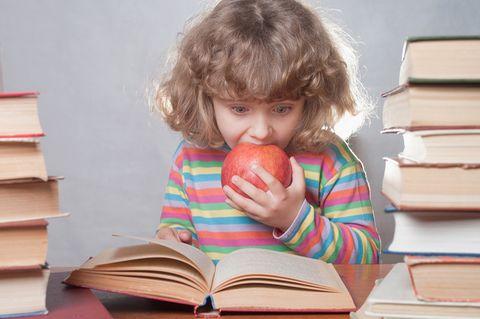 Junges Mädchen liest in einem dicken Buch