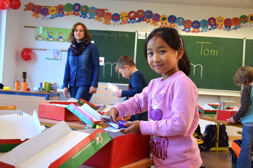 Natascha packt für Weihnachten im Schuhkarton ein Geschenk in der Schule