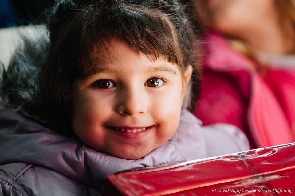 Ein Kinder freut sich über sein Geschenk im Schuhkarton