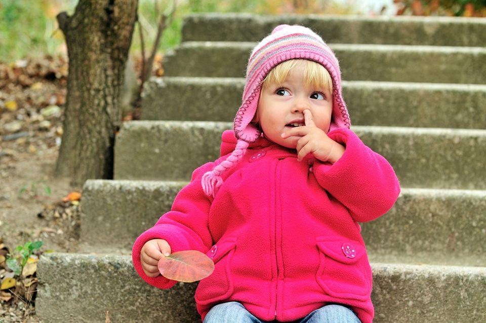 Kleines Mädchen auf einer Treppe bohrt in der Nase