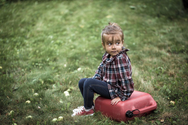 Ein kleines Mädchen schämt sich und sitzt allein auf einer Wiese
