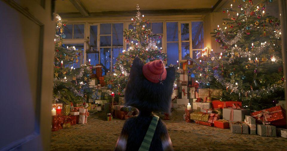 Findus im Wohnzimmer mit vielen Weihnachtsbäumen