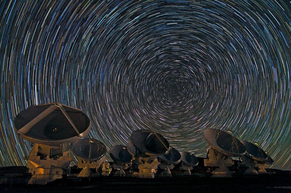 Antennen des ALMA-Teleskops und Sternenhimmel