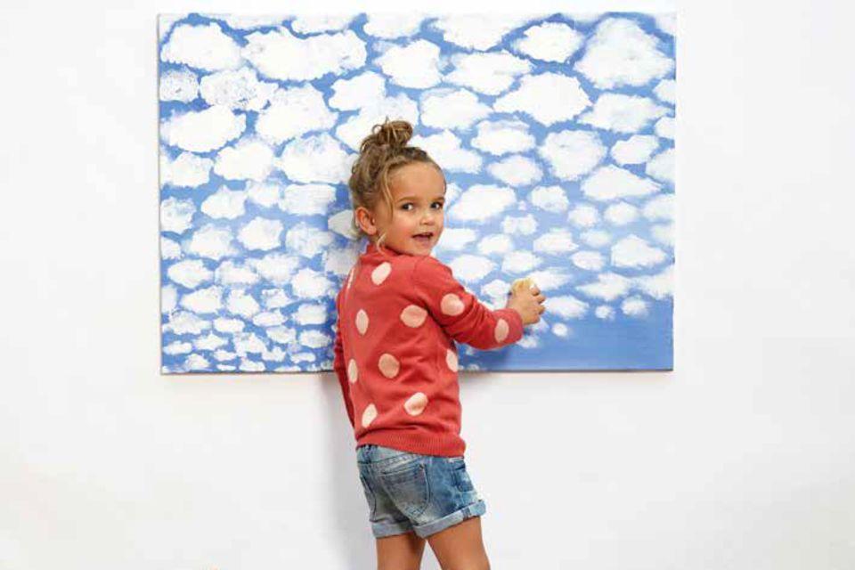 Ein Mädchen tupft mit einem Schwamm Wolken auf ein Bild