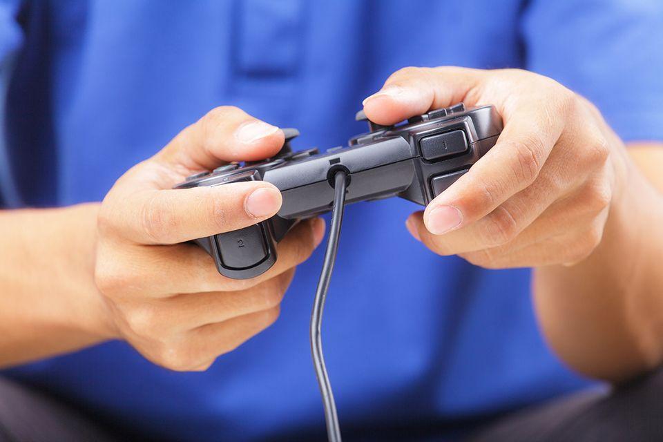 Mann spielt Playstation mit Controller