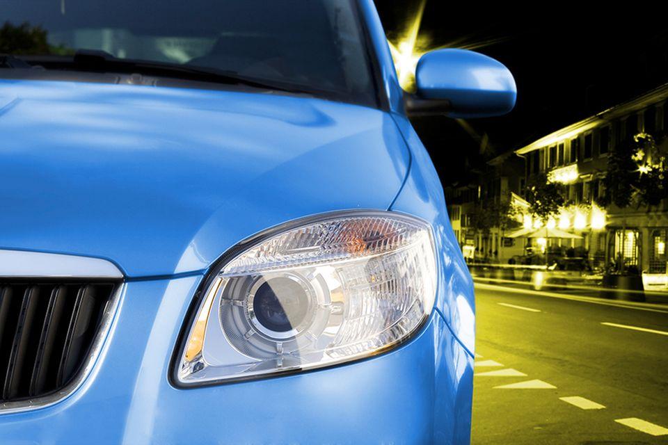 Ausschnitt eines blauen Autos, das durch die Nacht fährt