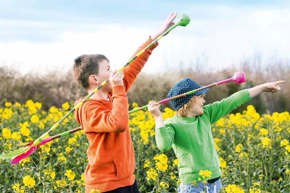 Kinder werfen auf einer Wiese Wurfspeere aus Ästen
