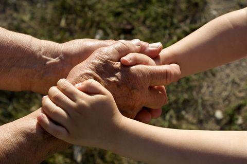 Kind und älterer Mensch halten sich an den Händen