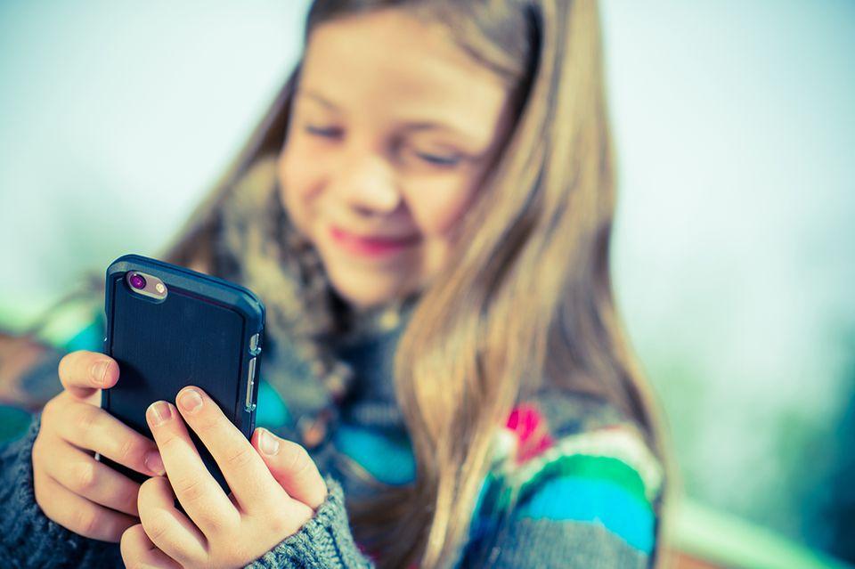 Ein Mädchen spielt auf dem Smartphone