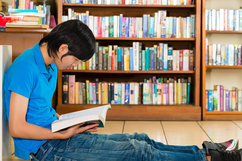 Junge liest in einem großen Buch vor einem Bücherregal
