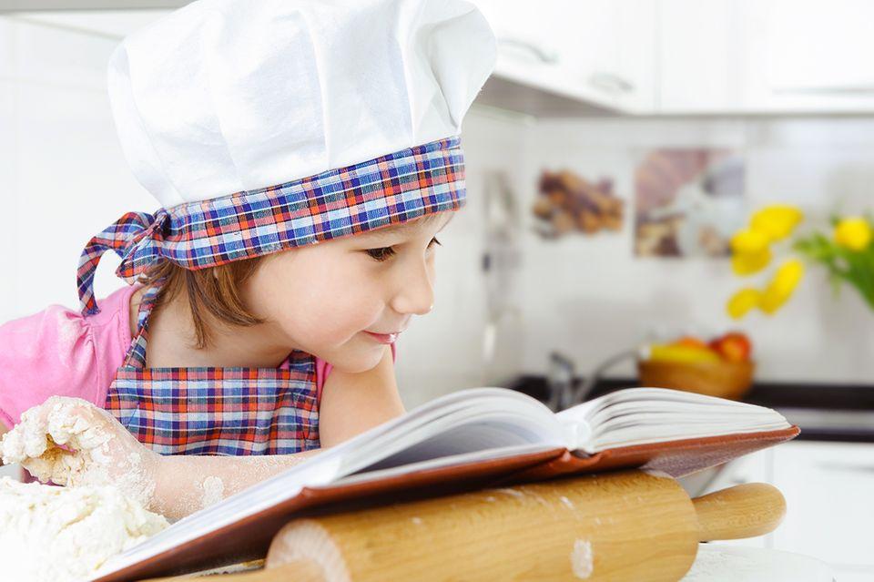 Kind mit Kochmütze und Kochbuch