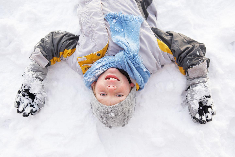 Jung liegt im Schnee